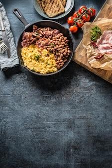 Engels ontbijt roerei gegrilde spek bonen en toast brood - top of view.