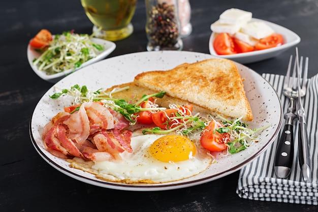 Engels ontbijt - toast, ei, bacon en tomaten en salade van microgreens.
