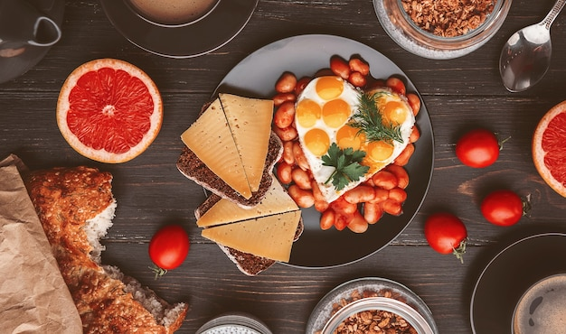 Engels ontbijt. worst, gebakken eieren en bonen in tomaat. koffie en brood in de buurt. chia met yoghurt en granola