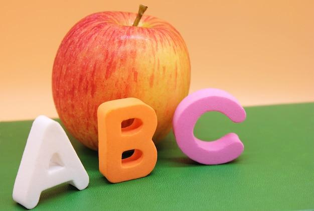 Engelse abc-alfabetletters naast boek en appel.