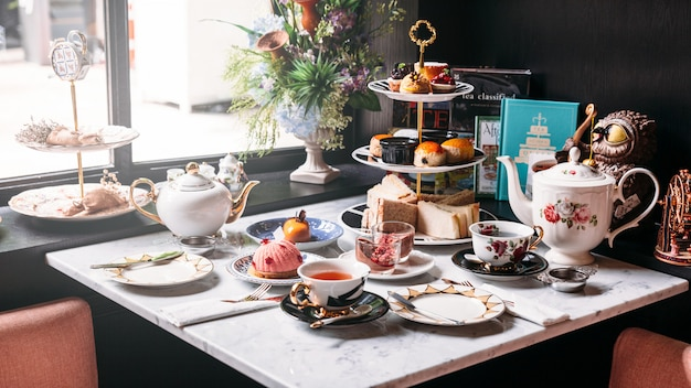 Engelse afternoon tea met warme thee, gebak, scones, sandwiches en mini-pasteien.