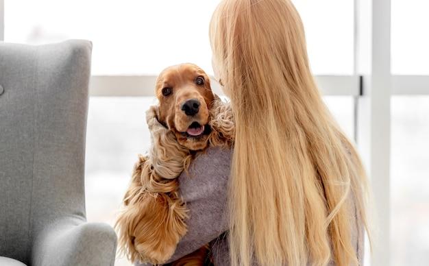 Engelse cocker spaniel hond met liefdevolle vrouw eigenaar zittend op de vloer thuis