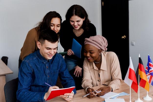 Engelse klasstudie met studenten uit verschillende landen: polen, duitsland, vs. teamwerk. werken met multi-etnische studenten. leraar studeert samen vreemde talen in de klas. studeren met laptop.