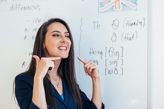 Engelse les leraar laat zien hoe de klanken moeten worden uitgesproken.
