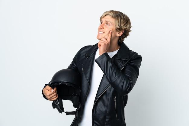 Engelse man met een motorhelm die een idee denkt terwijl hij omhoog kijkt