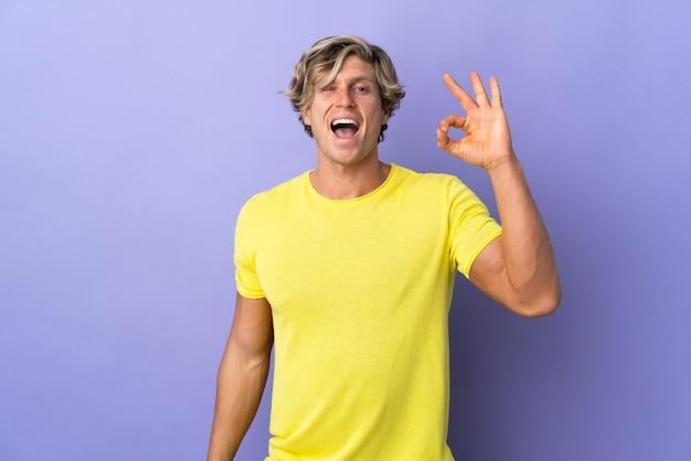 Engelse man op geïsoleerde paars met ok teken met vingers