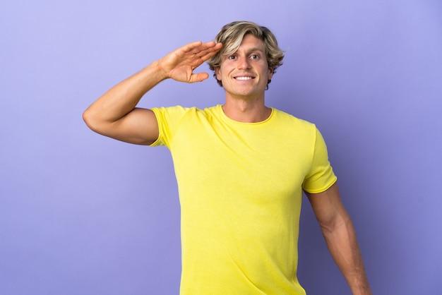 Engelse man op geïsoleerde paarse groet met hand met gelukkige uitdrukking