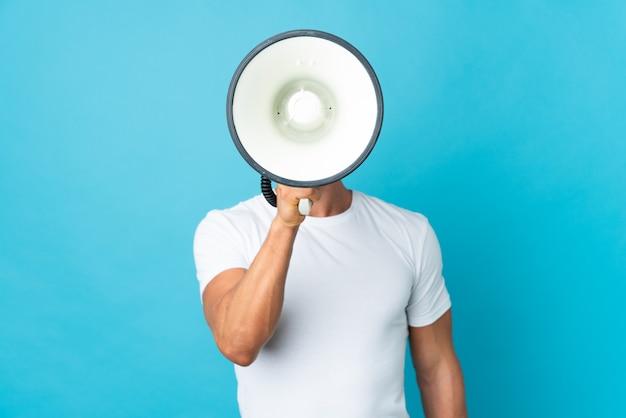 Engelse man over geïsoleerde blauwe muur die door een megafoon schreeuwt om iets aan te kondigen