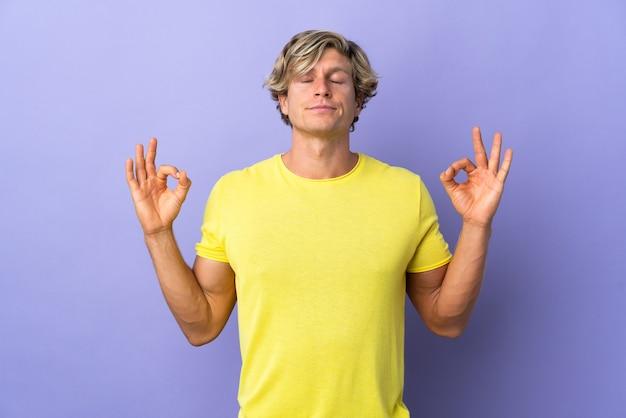 Engelse man over geïsoleerde paarse muur in zen-pose