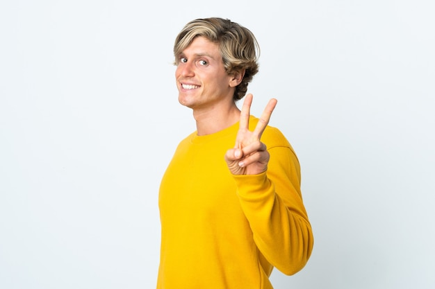 Engelse man over geïsoleerde witte achtergrond die en overwinningsteken glimlacht toont
