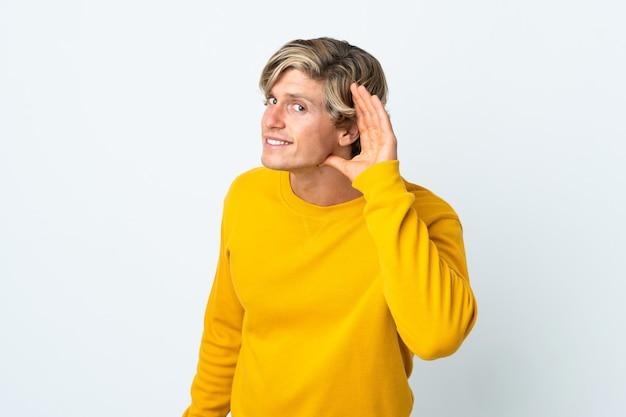 Engelse man over geïsoleerde witte achtergrond luisteren naar iets door hand op het oor te leggen