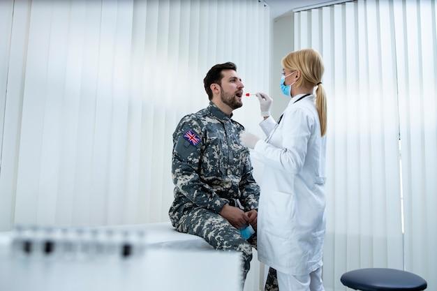 Engelse soldaat in uniform doet pcr-test bij dokterspraktijk tijdens covid19-virusepidemie