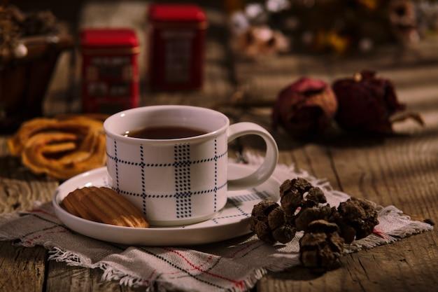 Engelse theetijd. kopje thee met koekjes op houten tafel, rustieke zelfgemaakte interieur.