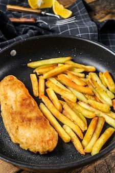 Engelse traditionele fish and chips-schotel met frietjes in een pan