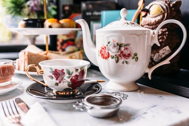 Engelse vintage porseleinen rozen-theesets inclusief theepot, theekop, bord, lepel en theefilter.