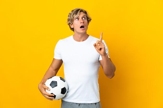 Engelse voetballer over geïsoleerde gele muur die een idee denkt die met de vinger omhoog wijst