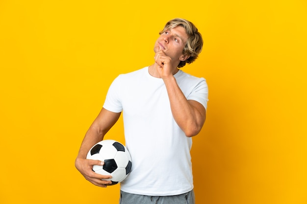 Engelse voetballer over geïsoleerde gele muur en omhoog kijkend