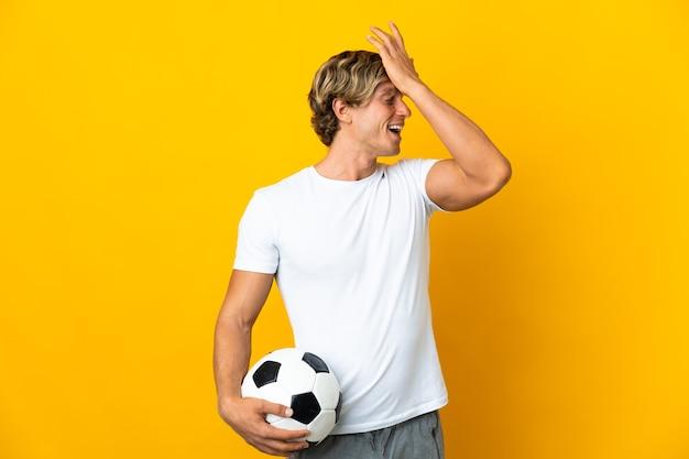 Engelse voetballer over geïsoleerde gele muur heeft iets gerealiseerd en de oplossing voor ogen