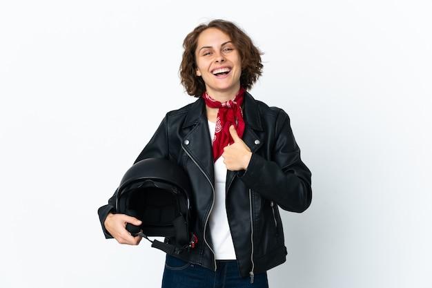Engelse vrouw die een motorhelm houdt die op witte ruimte wordt geïsoleerd die een duim omhoog gebaar geeft