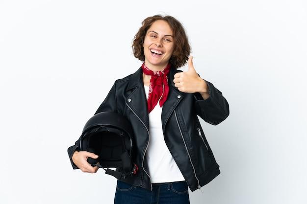 Engelse vrouw met een motorhelm op wit met duimen omhoog omdat er iets goeds is gebeurd