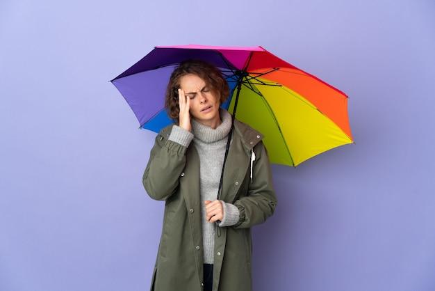 Engelse vrouw met een paraplu geïsoleerd op paarse muur met hoofdpijn