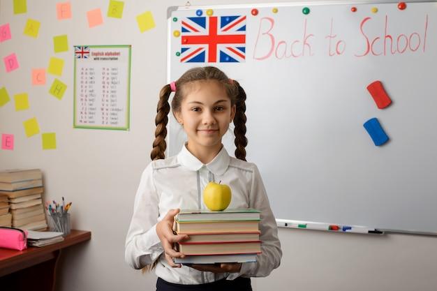 Engelse vrouwelijke student met boeken in haar handen