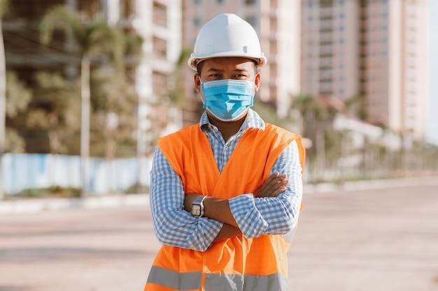 Engineer constructie draagt beschermend masker de verspreiding van covid 19-ziekten tijdens de inspectie op de bouwplaats. veiligheidsconcept