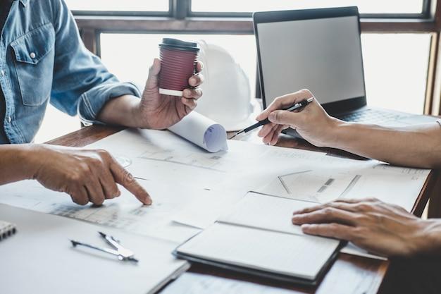 Engineer vergadering voor project werken met partner en hulpmiddelen op modelbouw en blauwdruk