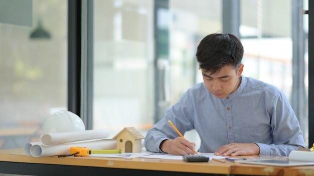 Engineering controleert de plattegrond op kantoor met apparatuur die op het bureau is geplaatst.