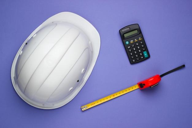 Engineering en bouwmachines op paarse achtergrond. bouwhelm, rekenmachine, liniaal. bovenaanzicht
