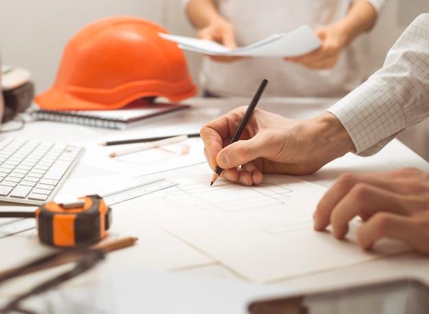 Engineering ontwerp. een schets tekenen op het bureaublad. teamwork.