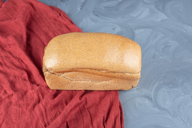 Enig broodbrood op een rood tafelkleed op marmeren oppervlakte.