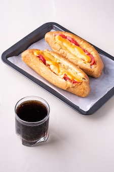 Enig glas coladrank met twee van de de troep verse worst van de hotdog fastfood verse de kaassaus die op bakplaat witte muur wordt geïsoleerd