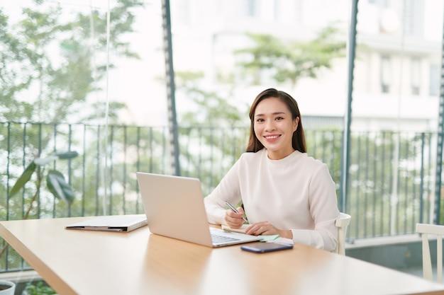 Enige gelukkige vrouwelijke bedrijfseigenaar met glimlach op telefoon Premium Foto