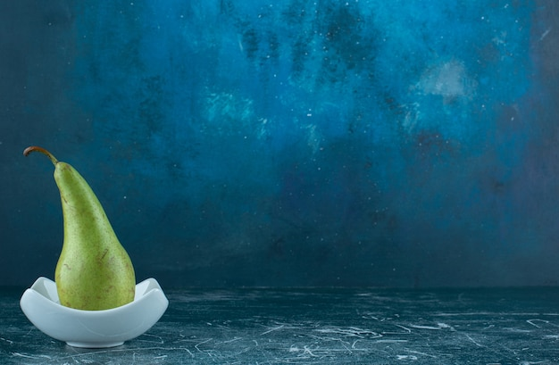 Enige groene peer in witte kom.