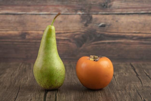 Enige hele peer en heerlijke dadelpruim op houten achtergrond