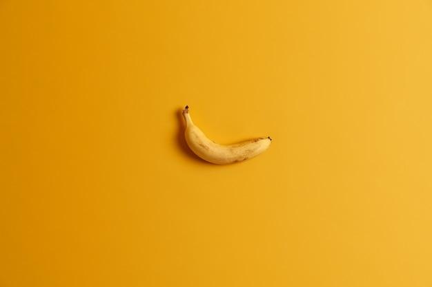 Enige rijpe heerlijke gele banaan die over studioachtergrond wordt geïsoleerd. felle kleur heerst. tropisch fruit voor je lekkere tussendoortje. smakelijk eetbaar product. lege ruimte voor tekst of informatie