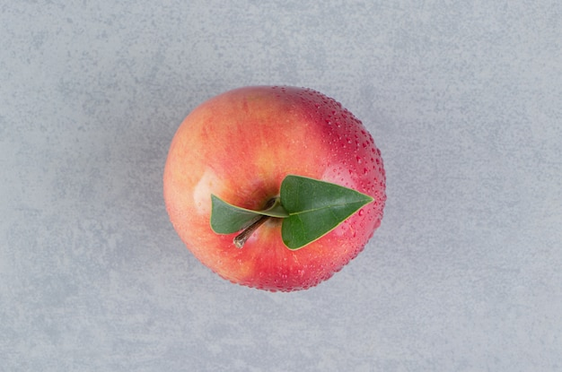 Enige rode appel op marmer.