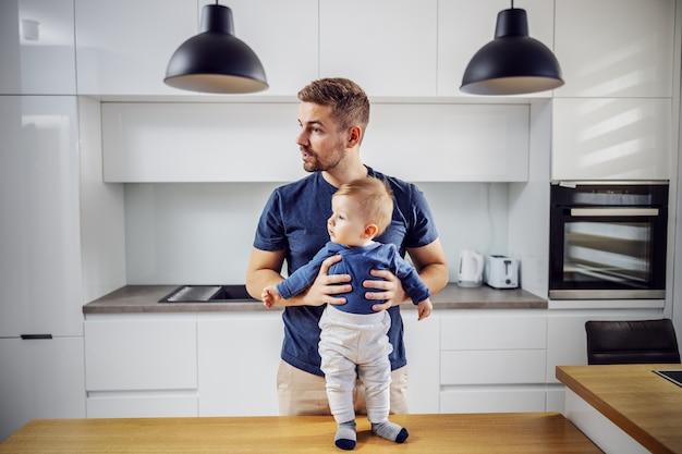 Enige vader die zich in keuken met zijn geliefde zoon bevindt. peuter permanent aan de keukentafel en vader houdt hem vast.