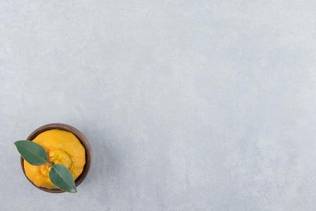 Enige verse mandarijn met bladeren in houten kom