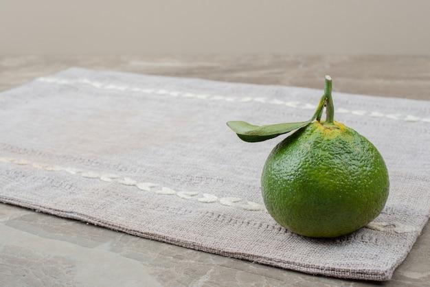Enige verse mandarijn op grijs tafelkleed.