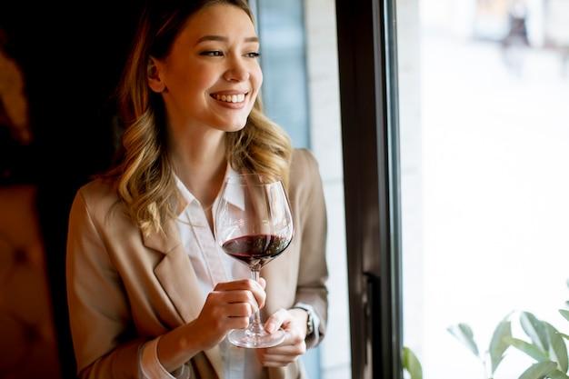 Enige vrij jonge vrouw met zich dichtbij venster bevinden en glas rode wijn die opzij kijken