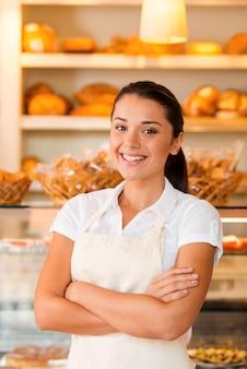Enkel vers gebak voor onze klanten. mooie jonge vrouw in schort die de armen gekruist houdt terwijl ze in de bakkerij staat