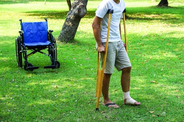 Enkelblessurepatiënten gebruiken krukken om te steunen op het gazon met een rolstoel erachter wheelchair
