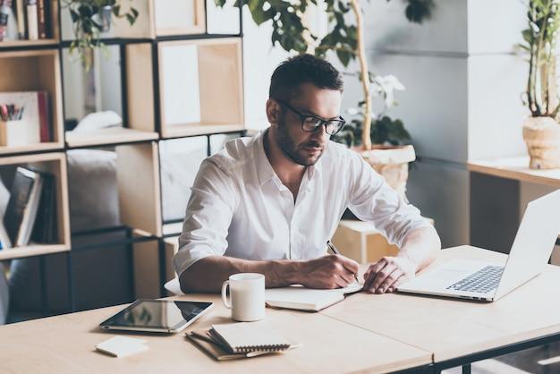 Enkele aantekeningen maken. geconcentreerde volwassen man die iets in een notitieblok schrijft terwijl hij op zijn werkplek op kantoor zit