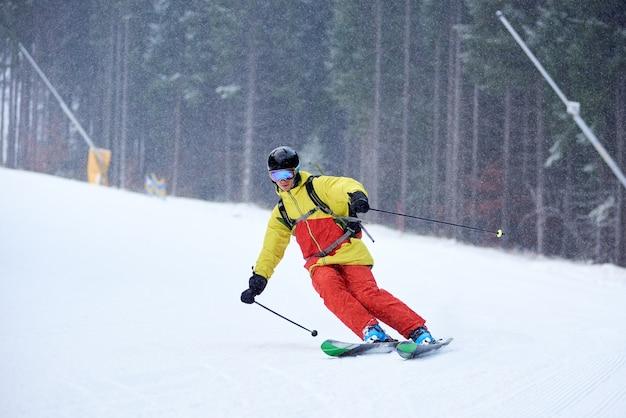Enkele afdaling van jonge mannelijke skiër alpineskiën en carve beurt op hoge beboste helling. skiën tijdens sneeuwval