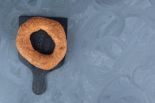 Enkele bagel op een zwarte houten plank op marmeren tafel.