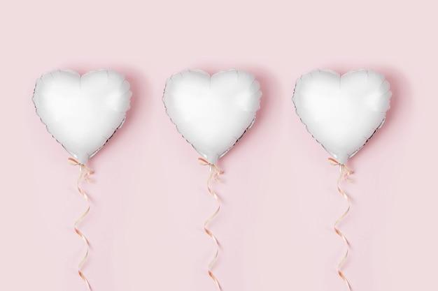 Enkele ballon van hartvormige folie op pastelroze ondergrond. liefdesconcept. vakantie vieren. valentijnsdag of bruiloft/vrijgezellenfeest decoratie. metalen ballon