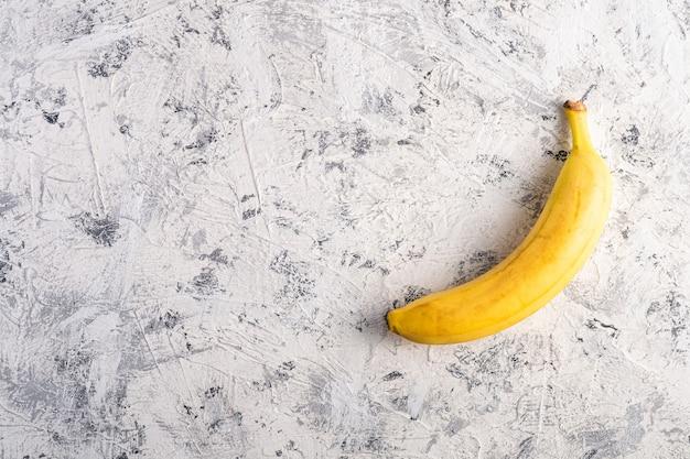 Enkele banaan fruit op witte gestructureerde achtergrond, bovenaanzicht kopie ruimte