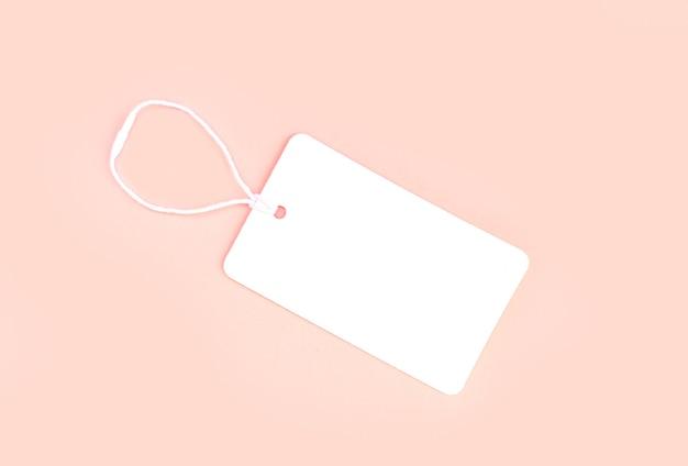 Enkele blanco witte papieren stoffen label of prijskaartje op lichtroze achtergrond bovenaanzicht